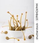 Small photo of Capers in a bowl on white wooden background. A bunch of marinated (pickled) edible fruits of Capparis. Caper berries are used as a garnish. Capers with selective focus, macro, close up. Copy space.