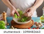 chef tears the lettuce leaves... | Shutterstock . vector #1098482663