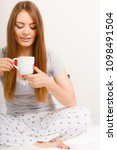 Small photo of Morning, awakening drink concept. Beautiful smiling young woman holding a cup of hot coffee or tea in bed indoor.