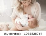 young mother holding her... | Shutterstock . vector #1098528764