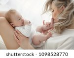 young mother holding her... | Shutterstock . vector #1098528770