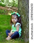 Small photo of Little girl looks downward with a somber expression on her face. She is barefoot and sitting all alone.