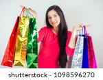 Small photo of beautiful happy brunette female with long hair shopaholic holding shopping bags . concept of shopaholism and sales