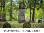 Small photo of Concord, MA / USA - May 19 2018: Alcott tombstone in Authors Ridge. USA flags and dogwood trees visible at the background.
