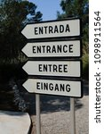 "Small photo of Multilingual entrance sign with ""Entrance"" in Spanish, English, French and German at a popular visitor attraction."