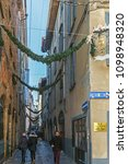 Small photo of BERGAMO, ITALY - 12 DECEMBER 2016: Old and small central street of medieval town (Citta Alta) with people walking and Christmas decoration.