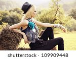 country girl is sitting on hay | Shutterstock . vector #109909448