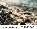 waves hit to the stones on the... | Shutterstock . vector #1099099340