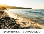 stony beach with waves and with ... | Shutterstock . vector #1099099370