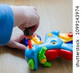 Small photo of A little child is collecting a toy motorcycle at home on the floor. Children's fingers skillfully operate with colored plastic details of a plaything. The kid is studying colors during the playing.