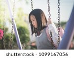 Stock photo lonely asian girl sitting on chain swing in the park 1099167056