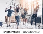 Small photo of So much fun! Full length of happy young people dancing while spending time at home with confetti flying everywhere