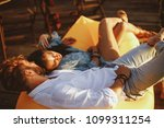 young couple lying in a lazy... | Shutterstock . vector #1099311254
