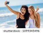 two young women taking selfie... | Shutterstock . vector #1099345496
