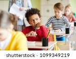 pensive schoolboy sitting by... | Shutterstock . vector #1099349219