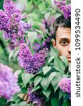 Small photo of Closeup odd unusual male portrait outdoor at nature in beautiful lilac bushes. Adult funny man face grimace surrounded by blooming flowers. Emotions and facial expxression. Clowning and fooling