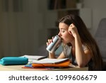 Small photo of Studious teen studying drinking energy beverage while is studying in the night at home