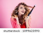 sexy girl with curly hair holds ... | Shutterstock . vector #1099623593