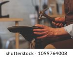 an elderly shoemaker at work in ... | Shutterstock . vector #1099764008