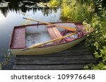 Little boat for one person stationed on pier - stock photo