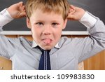 Funny preschool aged boy fooling in classroom - stock photo