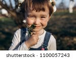 the small girl sniffs a flower   Shutterstock . vector #1100057243