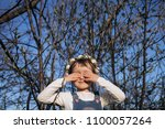 the small girl stands near trees | Shutterstock . vector #1100057264