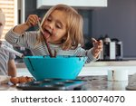 little girl licking spoon while ... | Shutterstock . vector #1100074070