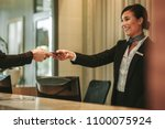 smiling receptionist behind the ... | Shutterstock . vector #1100075924