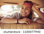 cheerful young woman sitting in ... | Shutterstock . vector #1100077940