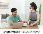 asian couple at home using a... | Shutterstock . vector #1100144090