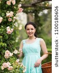 Stock photo portrait of young happy germany woman holding a basket near roses in a garden 1100180606