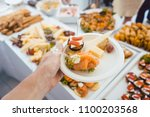 man helping himself on buffet... | Shutterstock . vector #1100203568