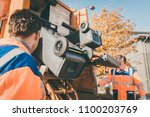 garbage removal worker emptying ... | Shutterstock . vector #1100203769