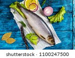 Stock photo whole herring on rustic deep blue wooden background top view 1100247500