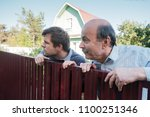 two caucasian men carefully... | Shutterstock . vector #1100251346