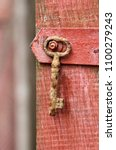 old rusty key on red wooden... | Shutterstock . vector #1100279243