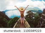happy female hiker standing on...   Shutterstock . vector #1100389223