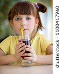 cute little girl drinks juice... | Shutterstock . vector #1100417960