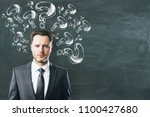 Small photo of Thoughtful businessman with drawn question marks on chalkboard background. Ask and inquiry concept