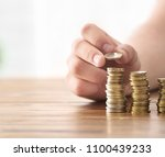 man stacking coins on table.... | Shutterstock . vector #1100439233