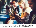 diverse friends using their... | Shutterstock . vector #1100446520