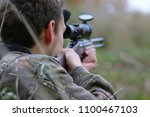 A man in camouflage and with guns in a forest belt on a spring hunt - stock photo