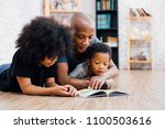 Small photo of African American father reading a fairy tale fable story for kids at home. Happy family lying on the floor indoors