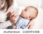 mother feeding baby boy with... | Shutterstock . vector #1100591408