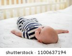 adorable baby lying in bed in... | Shutterstock . vector #1100637194