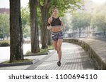 woman jogger exercising in town   Shutterstock . vector #1100694110