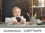 Small photo of Baby businessman doing paperwork at office. Little happy boy in formal showing tongue