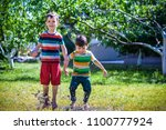 little boy and his brother play ... | Shutterstock . vector #1100777924