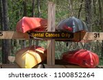 Small photo of Fully stocked camp site canoe rack. Multiple colored canoes ready for use